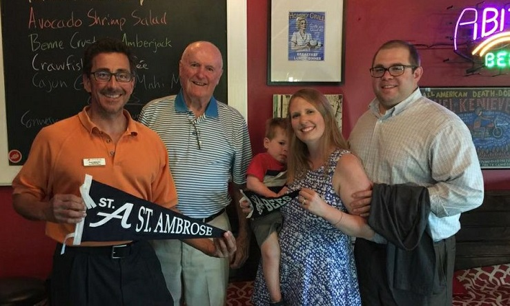 four alumni hold SAU pennant