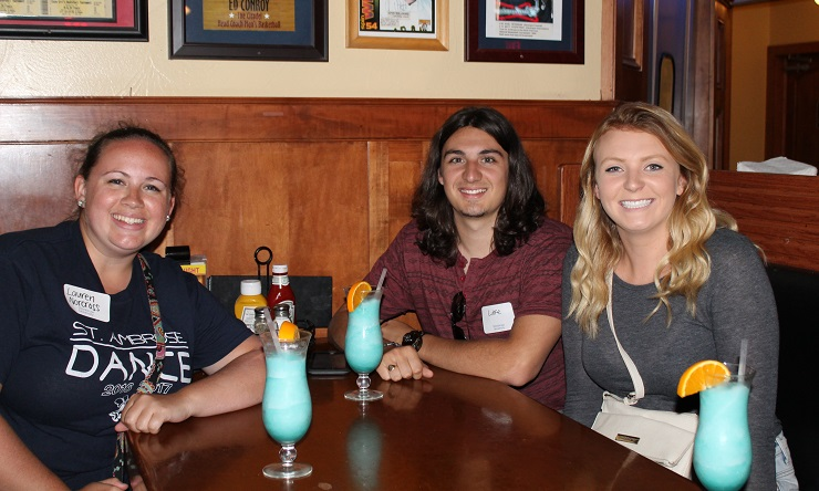 three alumni enjoy signature drink