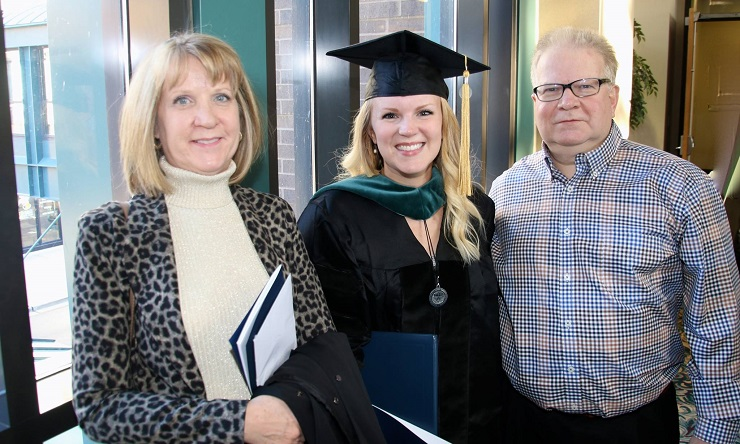 female student at graduation with her parents
