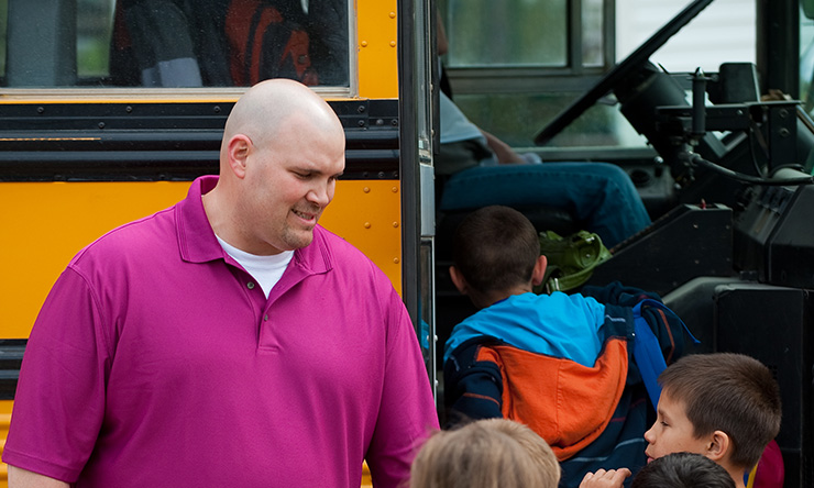 Student watching kids get on the bus
